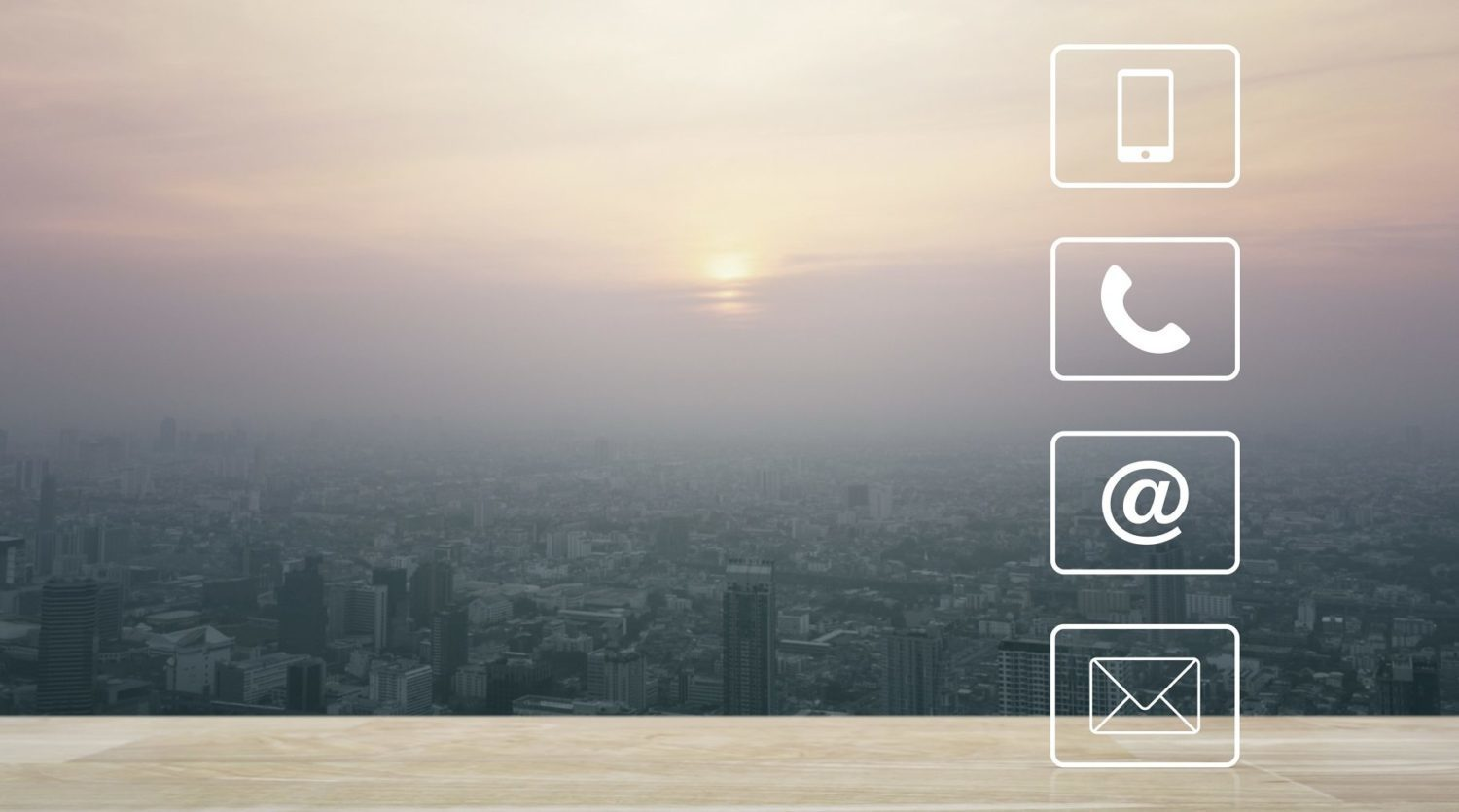 Telephone, mobile phone, address and email buttons on wooden table over aerial view of cityscape at sunset, vintage style, Business customer support and service concept